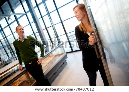 A couple smiling at each other in a supermarket, shallow depth of field, focus on woman. - stock photo