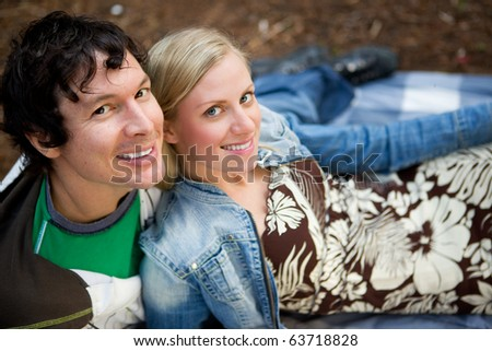 A couple smiling at the camera relaxing outdoors - stock photo