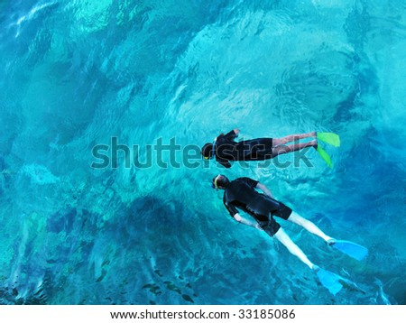 A couple snorkeling at the Great Barrier Reef - stock photo