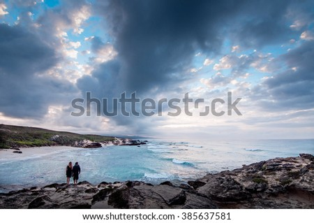 A couple standing at the ocean edge of a bay with a dramatic stormy sky overhead  - stock photo