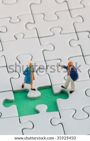 A couple standing in front of a missing jigsaw puzzle piece - stock photo