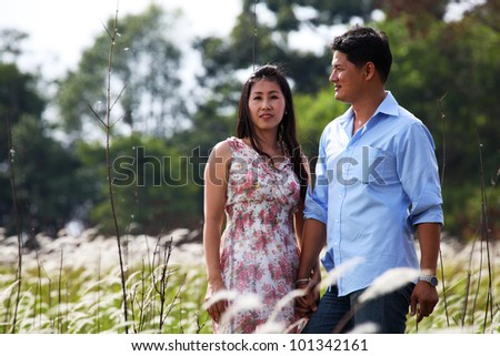A Couple Standing in Grassland, holding hands - stock photo