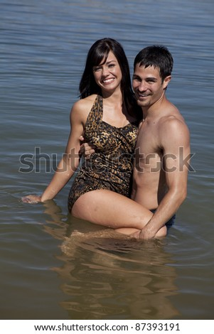 A couple standing in the water the man is holding his woman smiling. - stock photo