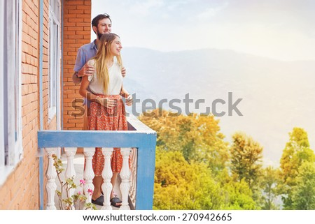 a couple standing on a balcony overlooking the hills in Nepal - stock photo