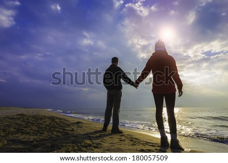 A couple standing on beach, holding hands./ Couple on a cloudy beach - stock photo