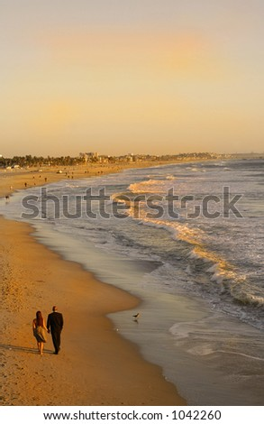 A couple stroll along a California beach at Sunset - stock photo