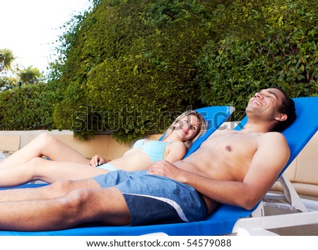 A couple suntanning on beach chairs beside a pool - stock photo