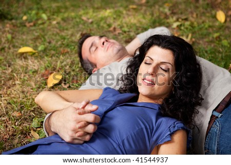 A couple taking a refreshing break outdoors in a park - sharp focus on female - stock photo