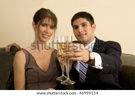 A couple toasts towards the camera. Focus is on the couples faces.