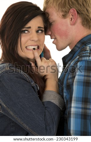 a couple together he is whispering in her ear, she has a confused expression. - stock photo