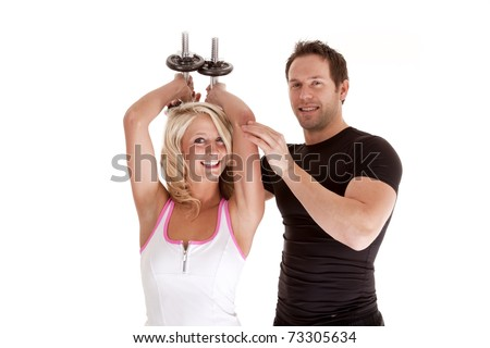 A couple together working out with weights with smiles on their faces. - stock photo