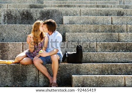 A couple traveling sit on the steps of a local landmark and kiss in the afternoon sunlight - stock photo