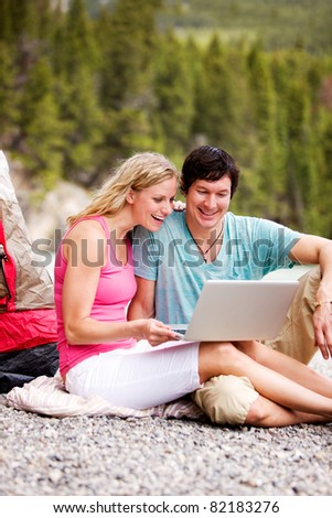 A couple using a laptop while on a camping trip - stock photo