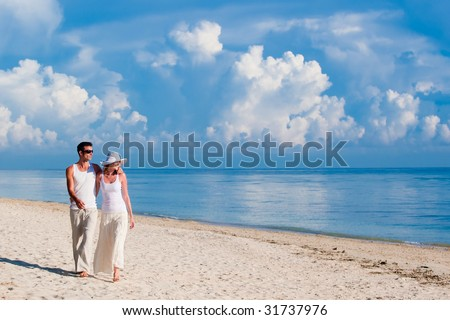 A couple walking along a sandy beach