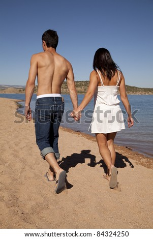 A couple walking along the beach holding hands. - stock photo