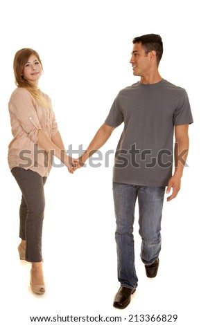 a couple walking and holding hands with a smile on their faces.