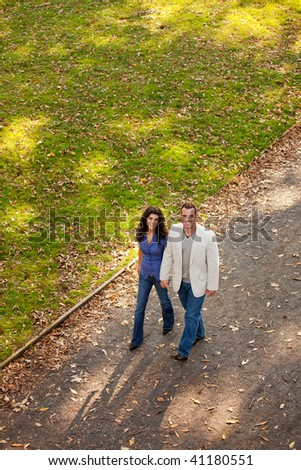 A couple walking in a park on a path - stock photo