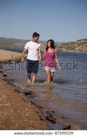 A couple walking in the water and holding hands looking in to each others eyes. - stock photo