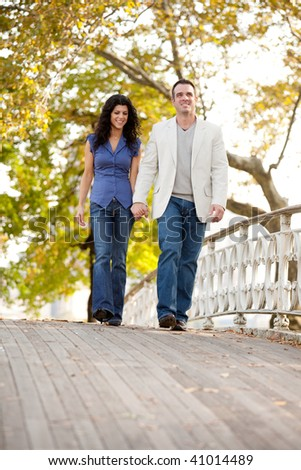 A couple walking on a bridge in a park - stock photo