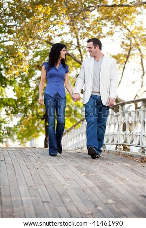 A couple walking on a bridge in a park