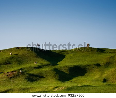 A couple walking on hills - stock photo