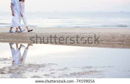 a couple walking on the beach - stock photo