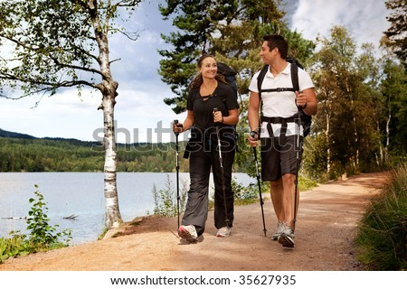 A couple walking on trail with backpacks - stock photo