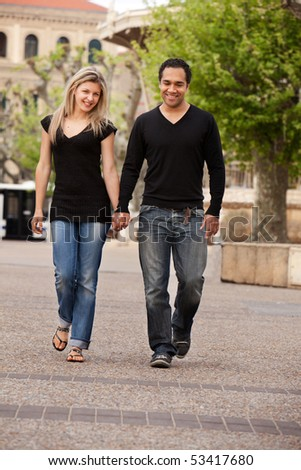 A couple walking outdoors in an urban landscape. - stock photo