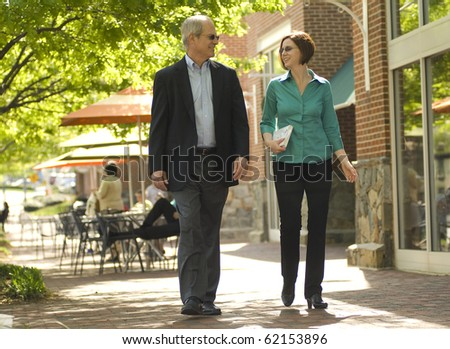 a couple walking through a business area as if on a lunch break