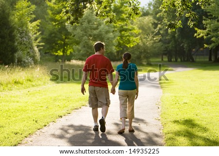 A couple walking through a park together. Rear view of them holding hands. Horizontally framed shot. - stock photo