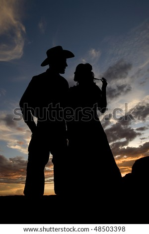 A couple walking together in the fields with a bold beautiful sky in the background.  The cowboy looks at his lovely ladie while she plays with her hair. - stock photo