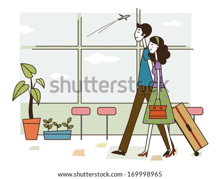 A couple walking together through an airport pulling luggage. - stock photo