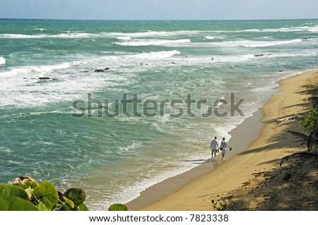 A couple walks along a deserted beach on a Caribbean island - stock photo