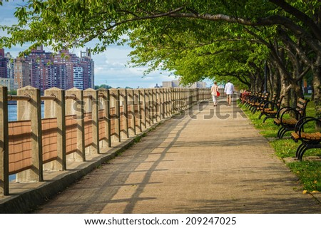 A couple walks along the East River near Southpoint Park on Roosevelt Island in Manhattan. - stock photo