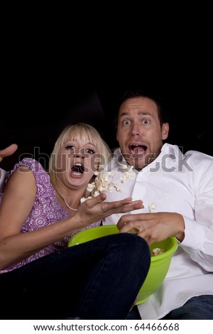 A couple watching a scary movie and it scared them so much that they threw the popcorn. - stock photo