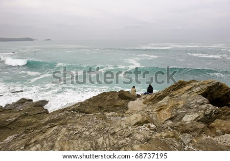 """A couple watching large winter waves in the UK coastal resort of Newquay. This is """"Little Fistral"""" beach. - stock photo"""