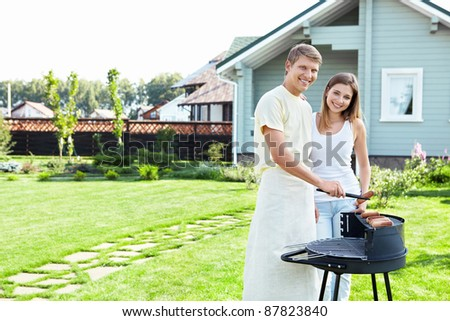 A couple with a barbecue on the lawn - stock photo