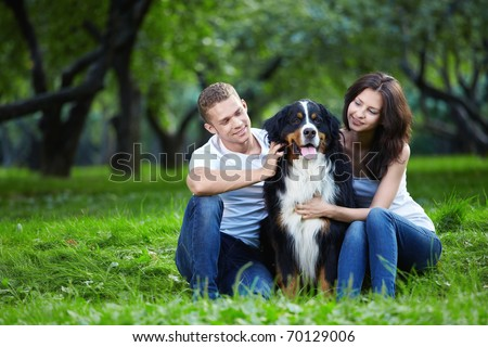 A couple with a dog in the park - stock photo