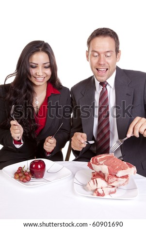 A couple with a lot of food in front of them. - stock photo