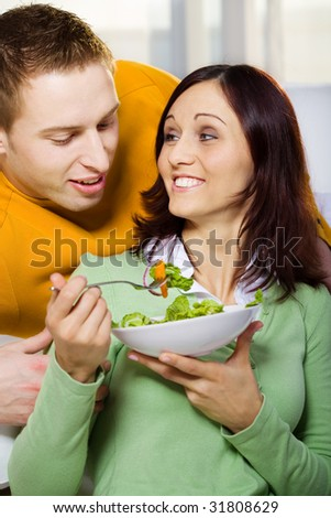 a couple with salad in the living room