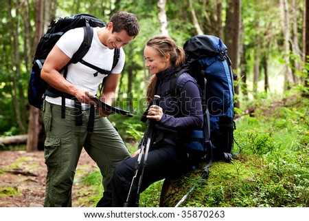 A couple with smiles looking at a map in the forest - stock photo