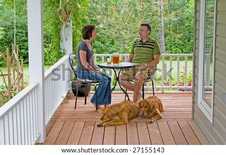 A couple with their dogs enjoying a glass of ice tea on their porch - stock photo