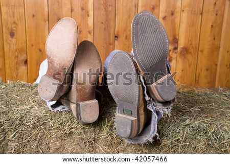 A couple with their feet side by side on a hay stack. - stock photo