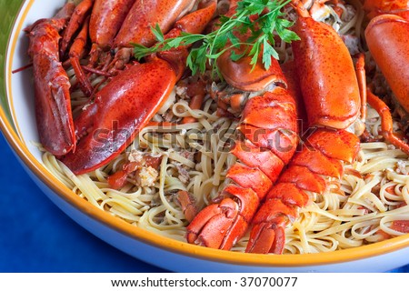 A course of linguine pasta with red lobsters on a blue background - stock photo