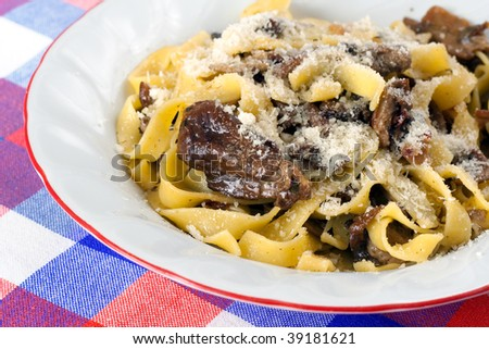 A course of pasta tagliatelle with fresh Porcini mushrooms and grated Parmiggiano - stock photo