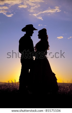 A cowboy and a woman are holding each other in the sunset.