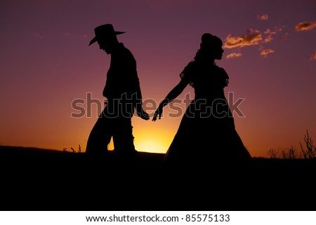 A cowboy and a woman are silhouetted in the sunset as they walk away from each other.