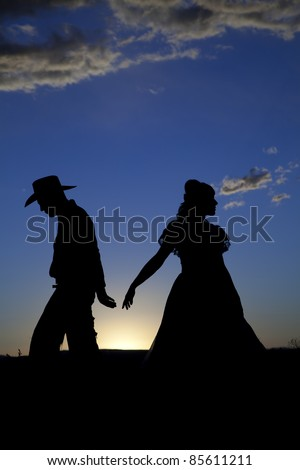 A cowboy and a woman are silhouetted in the sunset as they walk away from each other. - stock photo