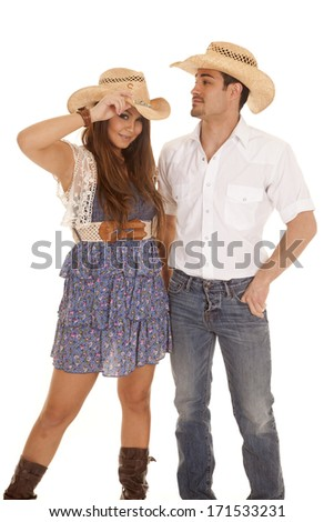 A cowboy and cowgirl standing together holding on to each other. - stock photo