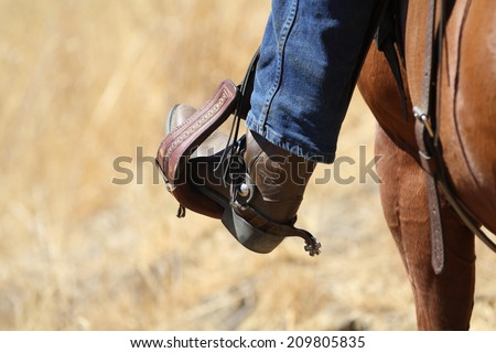 A cowboy boot in saddle stirrup. - stock photo